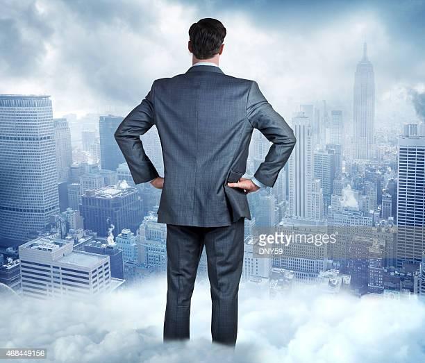Homme d'affaires debout dans les nuages qu'il examine grande ville