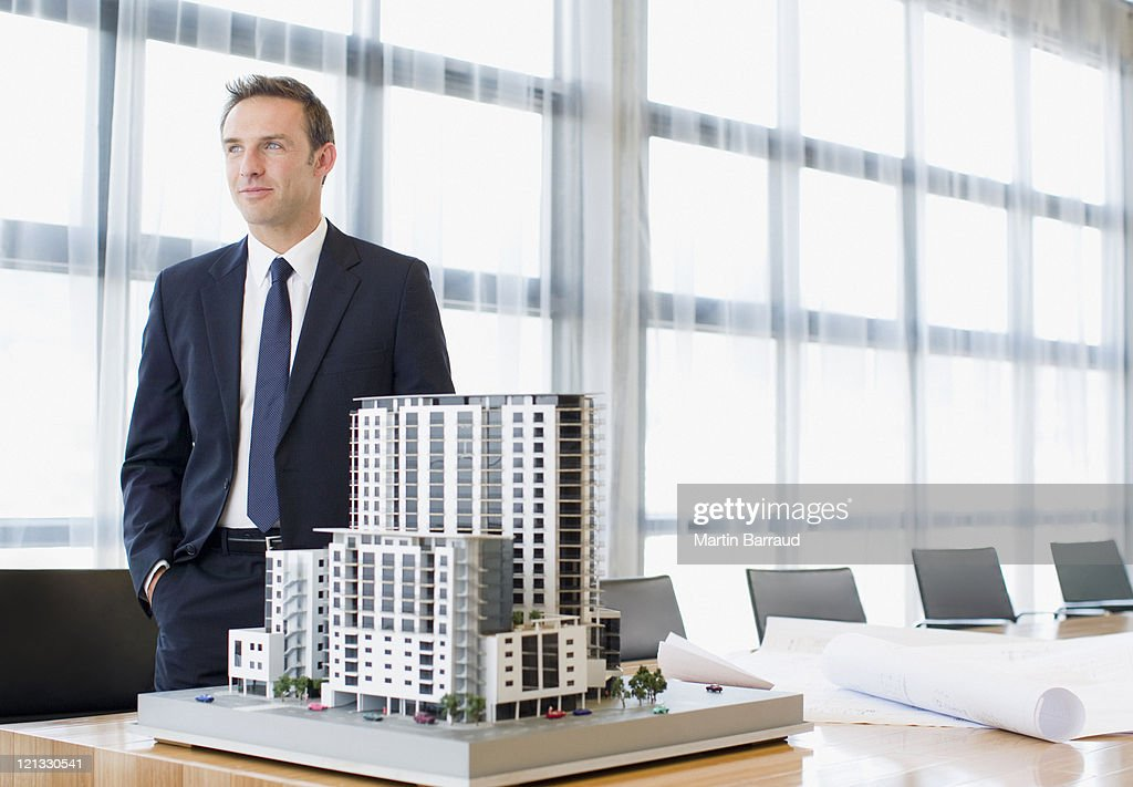 Businessman standing in conference room with model building : Stock Photo