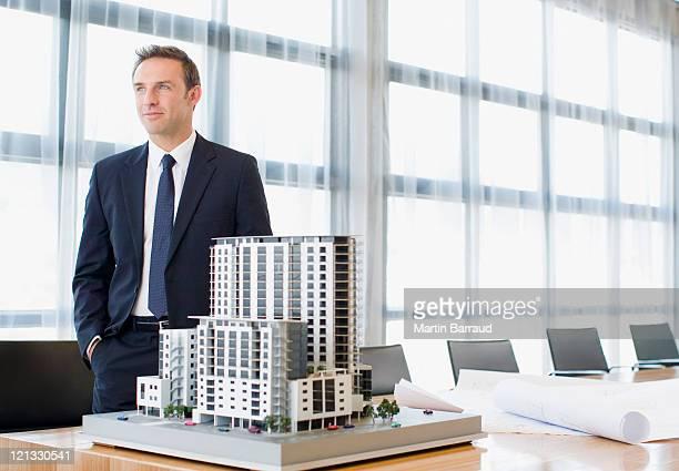 Hombre de negocios de pie en la sala de conferencias con construcción del modelo