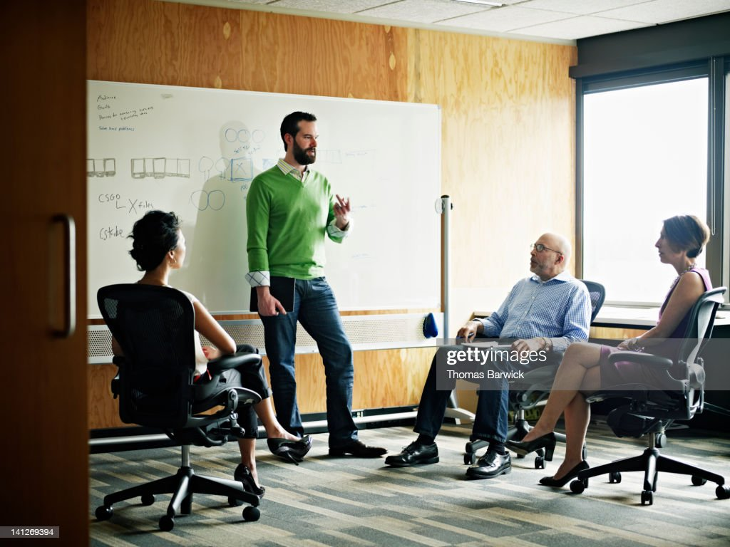 Businessman standing in discussion with coworkers