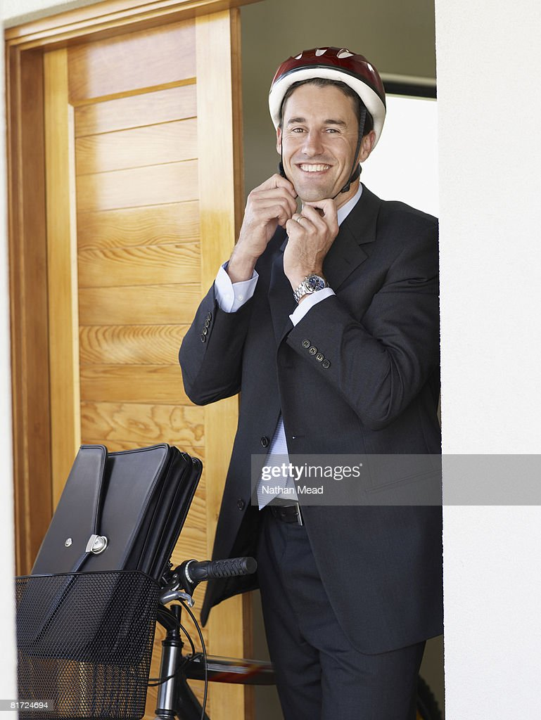 Businessman standing in doorway with bicycle putting on helmet and smiling : Stock Photo