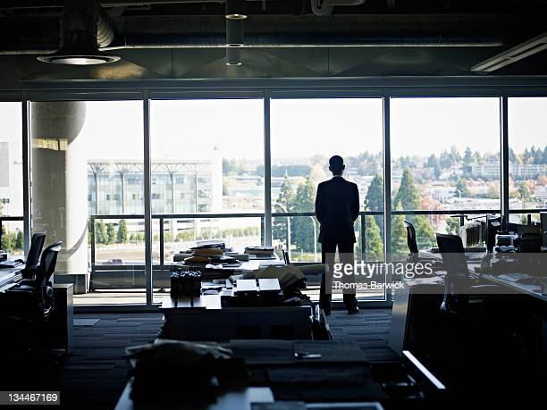Businessman standing in empty office looking out