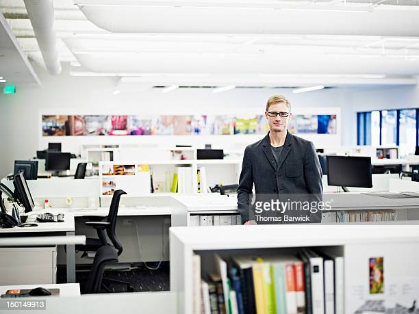 Businessman standing in empty office smiling