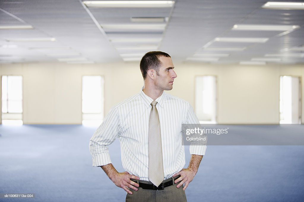Businessman standing in empty office with hand on hips : Stock Photo