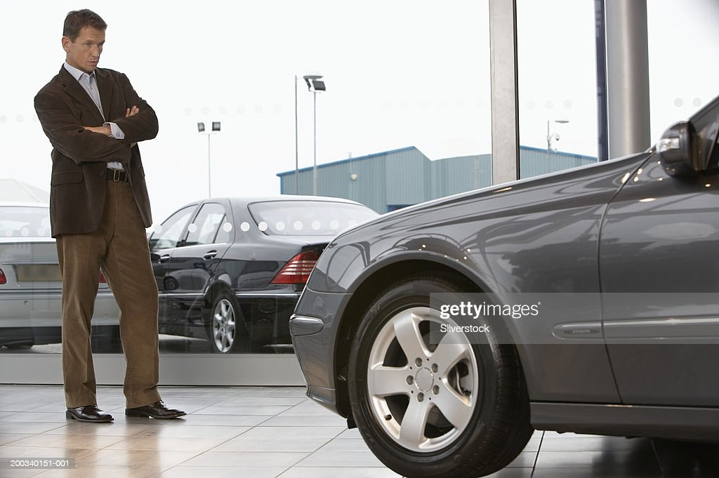 Businessman standing in front of car in showroom with arms folded : Stock Photo