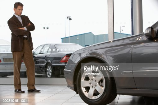 Businessman standing in front of car in showroom with arms folded : Foto de stock
