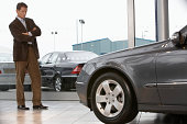 Businessman standing in front of car in showroom with arms folded