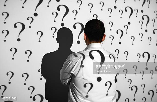 Businessman standing in front of question marks