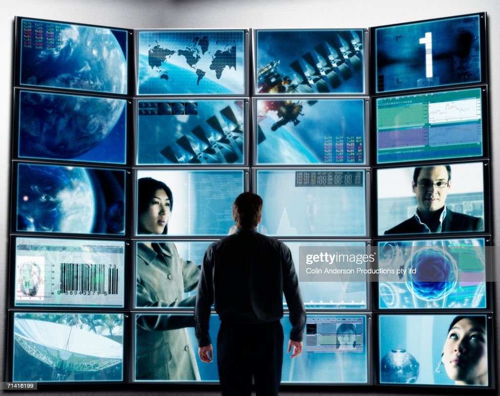 Businessman standing in front of television screens displaying technology : Stock Photo
