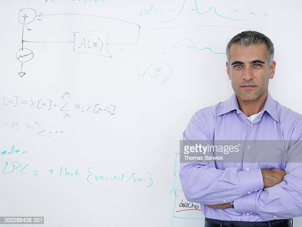 Businessman standing in front of whiteboard, arms crossed, portrait