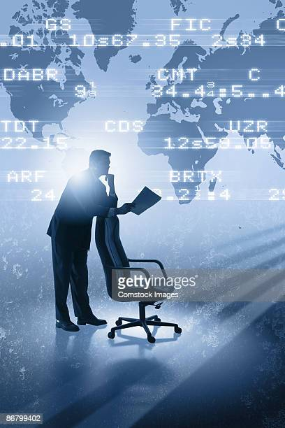 Businessman standing in front of world map and stock quotes