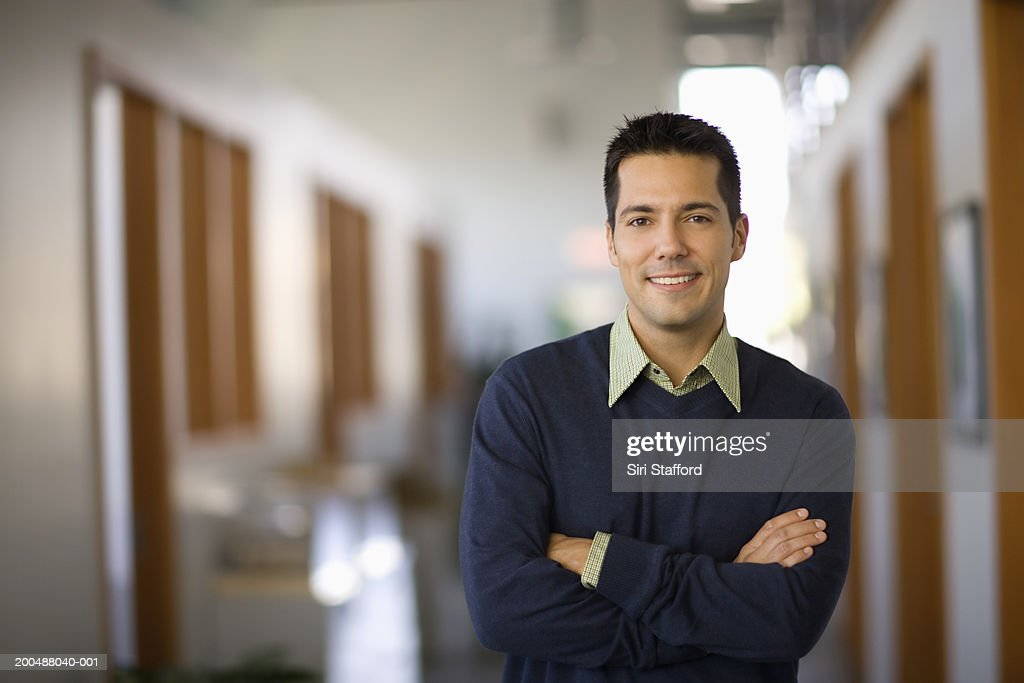 Businessman standing in hallway of office, arms crossed