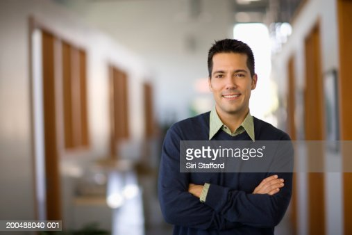 Businessman standing in hallway of office, arms crossed : Stock Photo