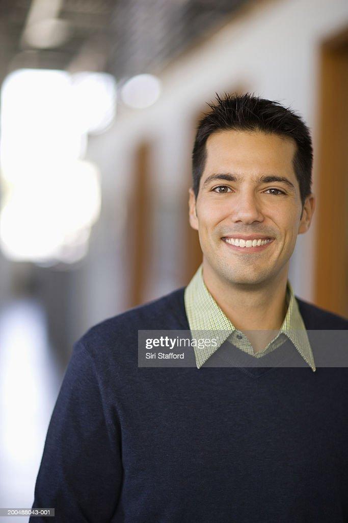 Businessman standing in hallway of office, portrait : Stock Photo