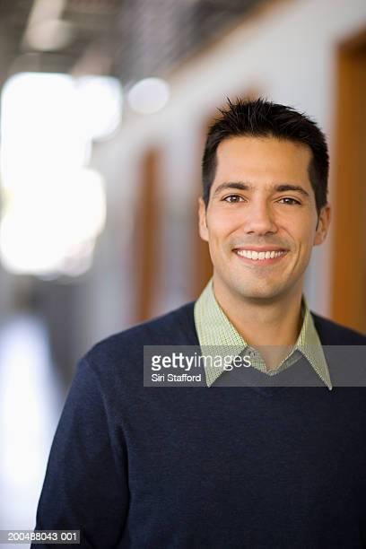 Businessman standing in hallway of office, portrait