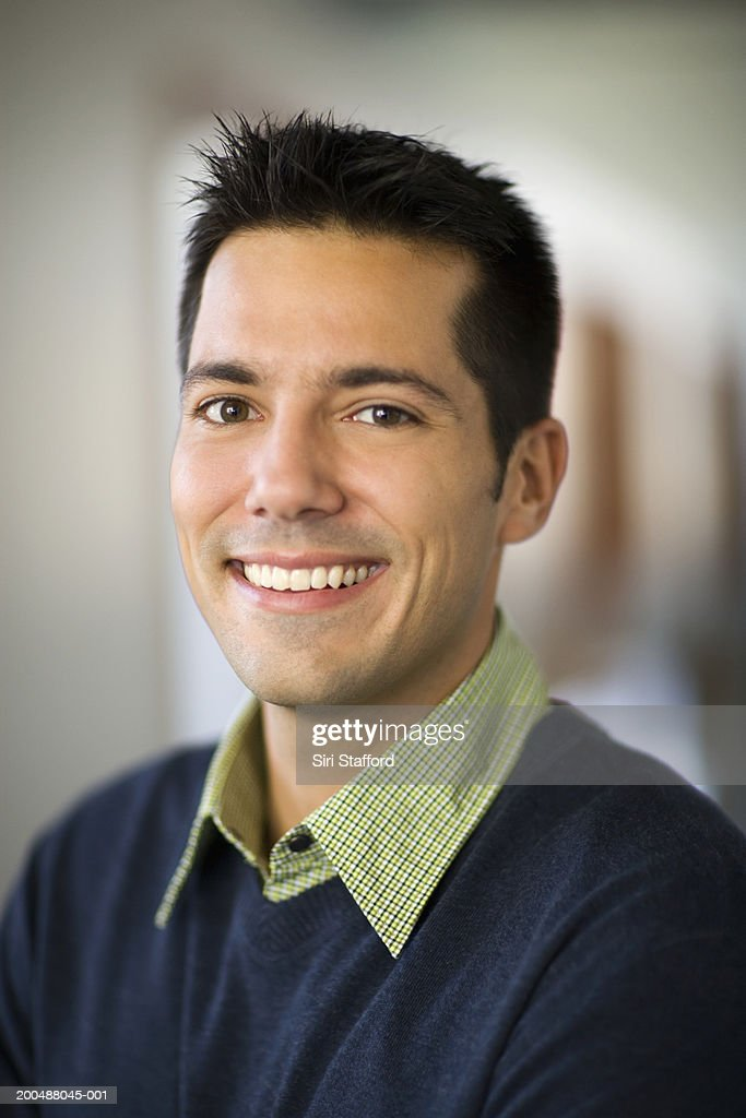 Businessman standing in hallway of office, smiling : Stock Photo