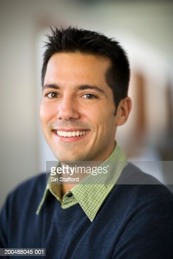 Businessman standing in hallway of office, smiling