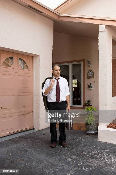 A businessman standing in his driveway looking away
