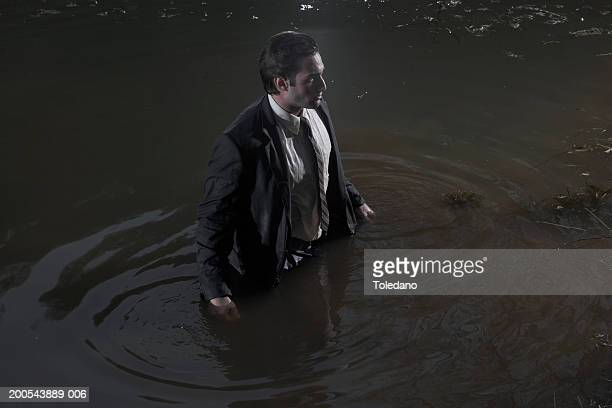 Businessman standing in lake, side view
