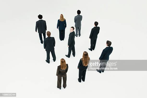 Businessman standing in midst of other anonymously dressed professionals
