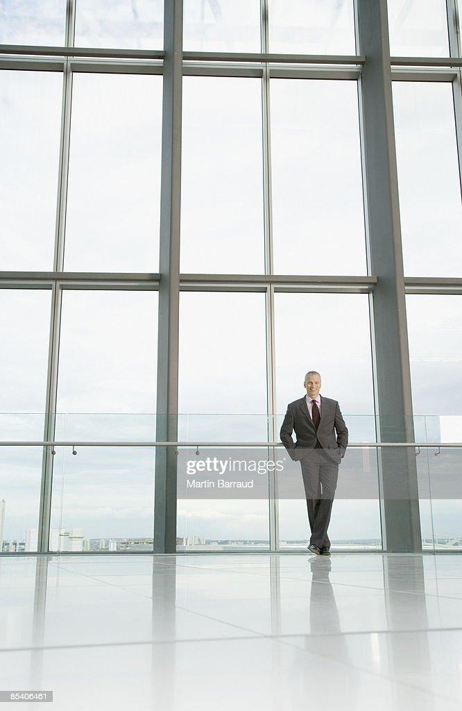 Businessman standing in modern lobby : Stock Photo