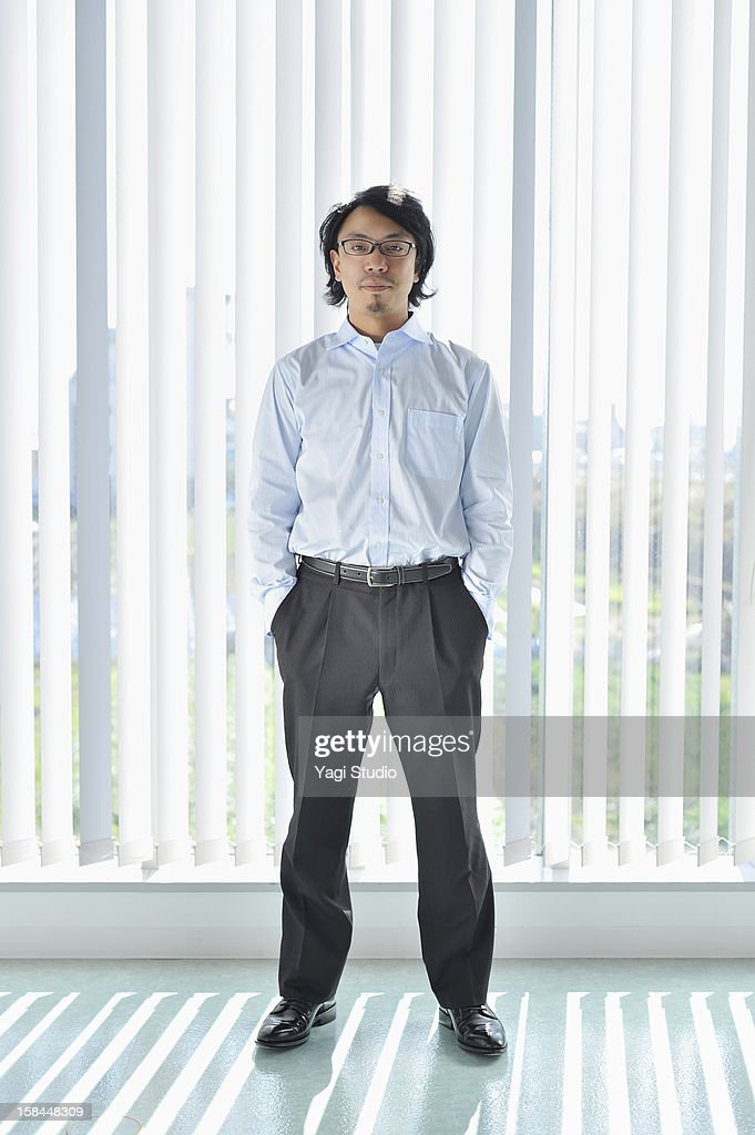 Businessman standing in office hall : Stock Photo