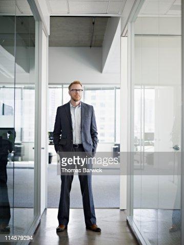 Businessman standing in office hallway : ストックフォト