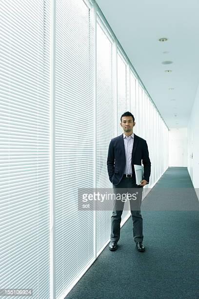 Businessman standing in office hallway
