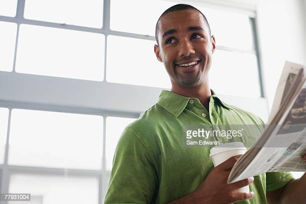 Businessman standing in office holding coffee cup and newspaper