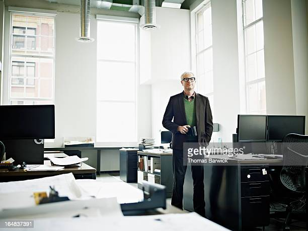 Businessman standing in office holding coffee cup