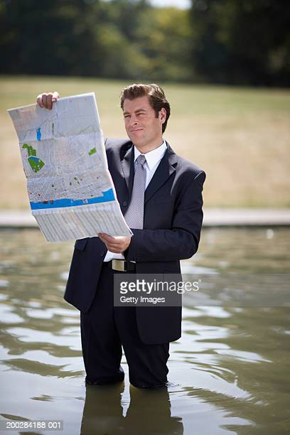 Businessman standing in pond, reading map