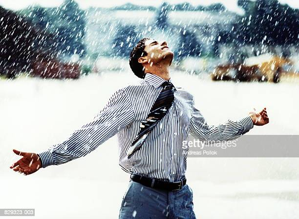 Businessman standing in pouring rain, spreading arms