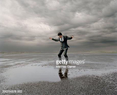 Businessman standing in puddle of water, arms stretched out : Stock Photo