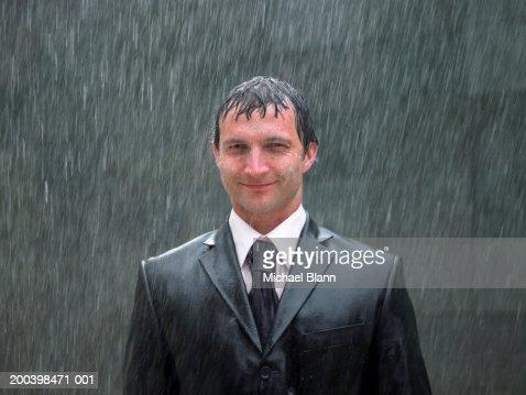 Hombre de negocios de pie en la lluvia, sonriendo, retrato, primer plano