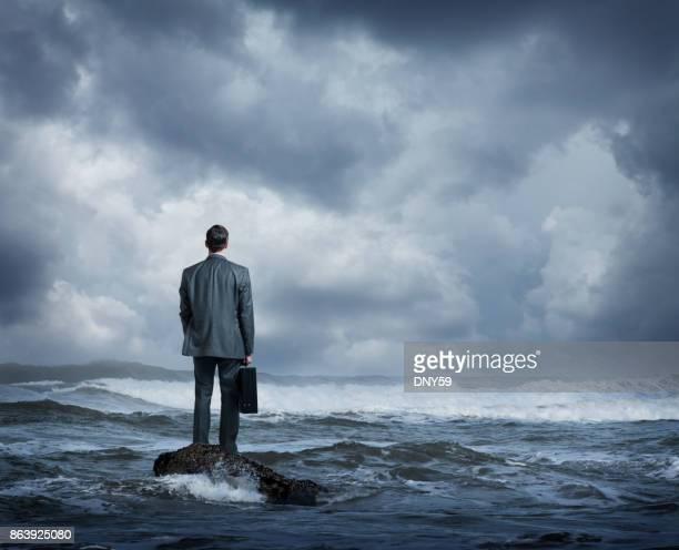 Businessman Standing In Rough Ocean Surf