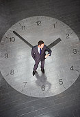 Businessman standing in standing in center of large clock and checking time on wristwatch