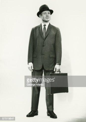 Businessman standing in studio, (B&W), portrait