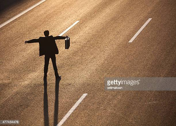 Businessman standing in the middle of highway and stopping traffic