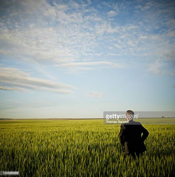 Businessman standing in wheat field hands on hips