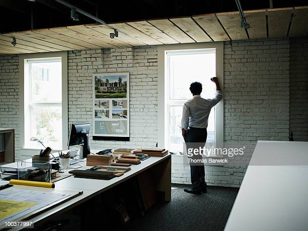 Businessman standing looking out window of office