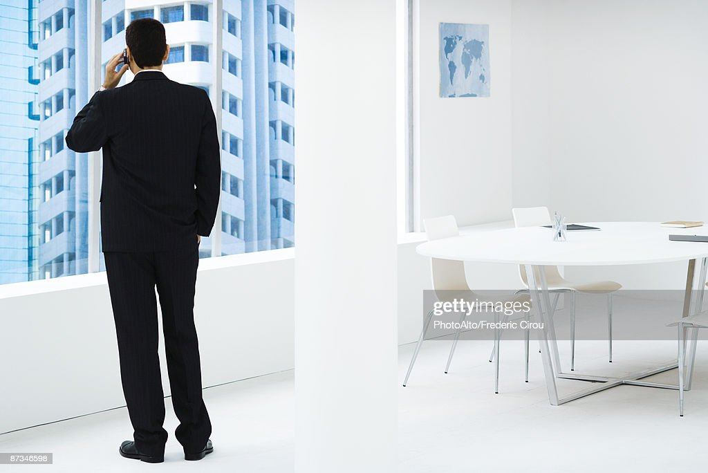 Businessman standing, looking out window, using cell phone : Stock Photo
