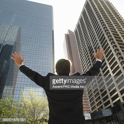 Businessman standing near buildings, arms outstretched, rear view : Stock Photo