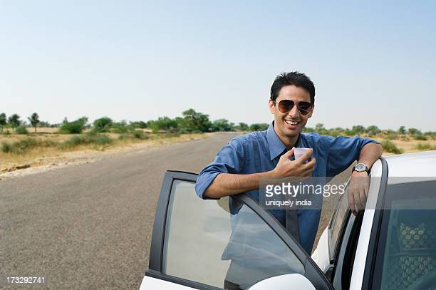 Businessman standing near his car and drinking tea
