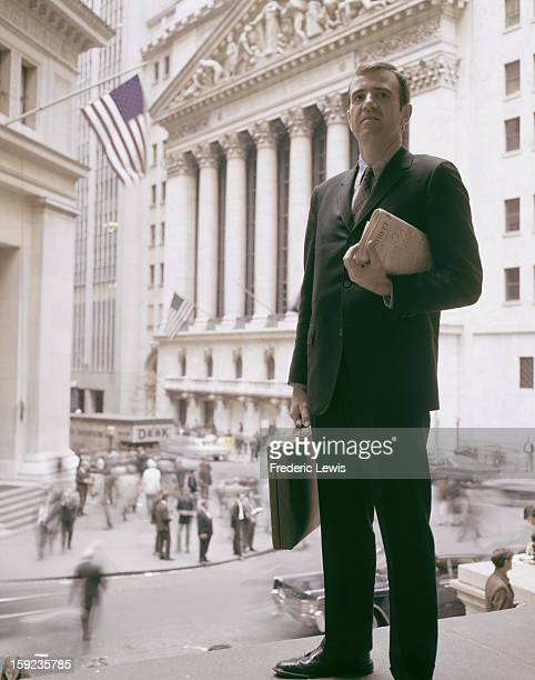 A businessman standing near the New York Stock Exchange on Wall Street Manhattan New York City circa 1965 He is holding a copy of the 'Wall Street...
