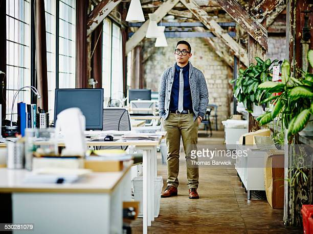 Businessman standing near workstations in office