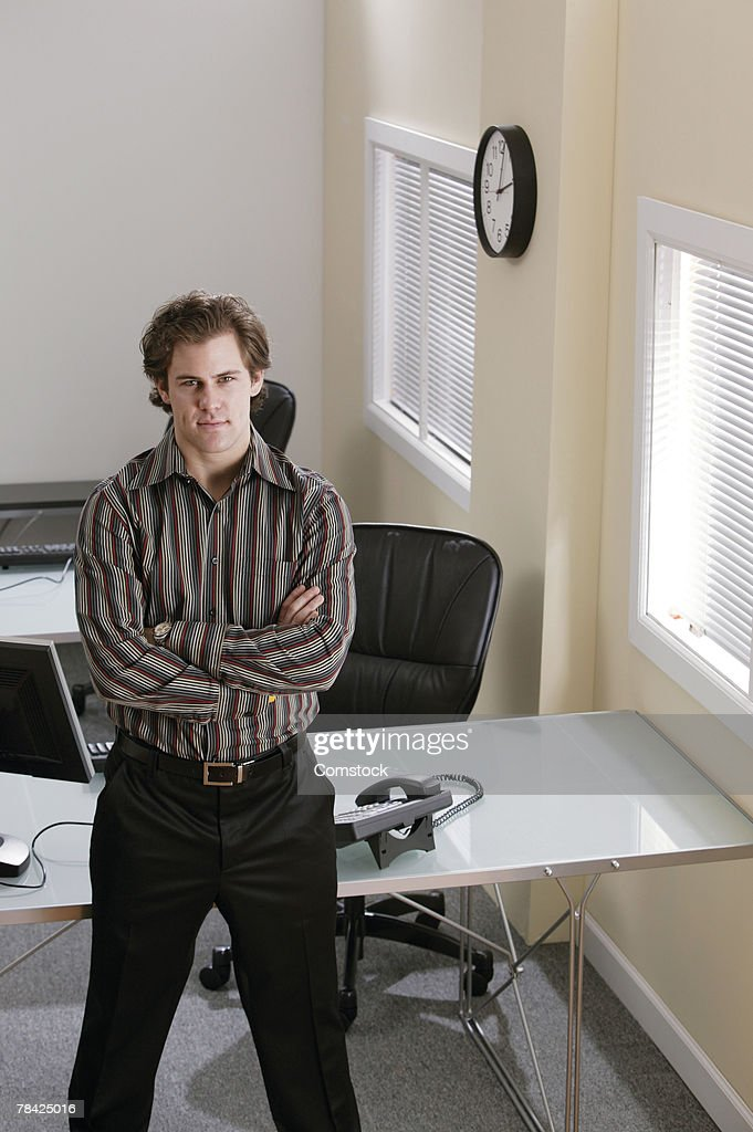 Businessman standing next to desk in office : Stock Photo