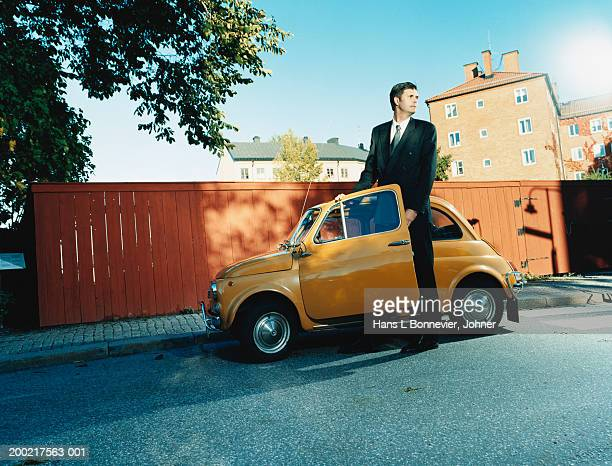Businessman standing next to small car in street