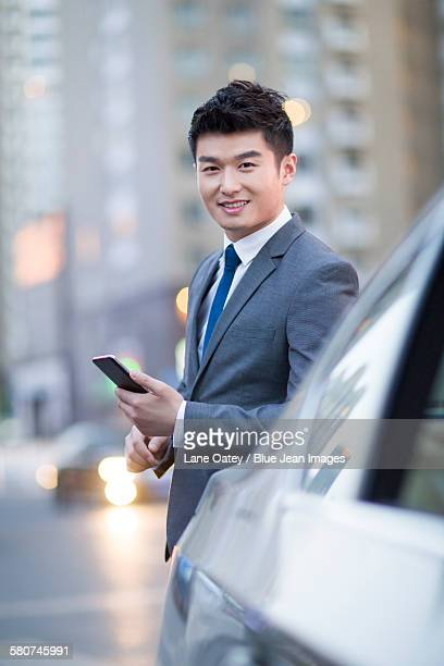 Businessman standing next to the car with smart phone