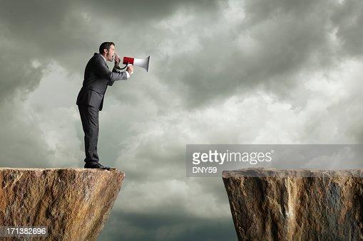 Uomo d'affari in piedi su una scogliera urlando in un megafono