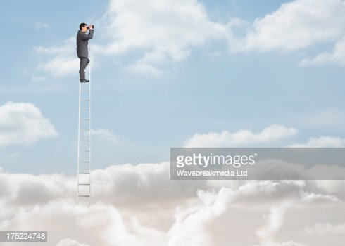 Businessman standing on a ladder over the clouds : Stock Photo